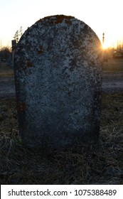 An old rustic tombstone with the sunset behind.
