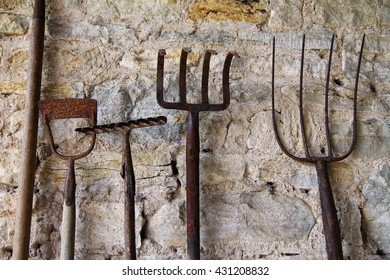 Old rustic tools against a stone wall