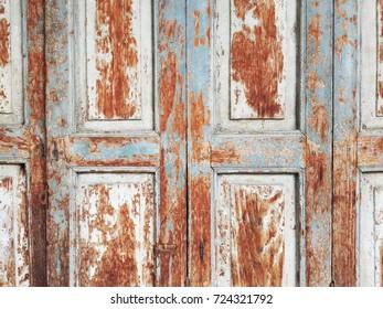 Old rustic wood door with peeling colour