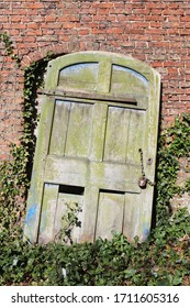 Old rustic wooden door with padlock and chain and broken rusty hinges