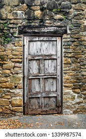 An old rustic wooden door is see in a stone wall of an old Spanish Mission in San Antonio, Texas.