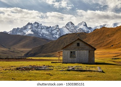 Old rustic wooden house white in the valley with snow mountain peaks near Kel Suu Lake in Naryn region, Kyrgyzstan
