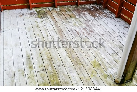 Old rustic wooden planks on balcony deck with green moss