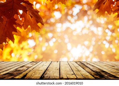 Old rustic wooden table with autumn leaves blur background. Seasonal thanksgiving, halloween and fall holiday tabletop product display. Vintage empty desk in nature forest montage.