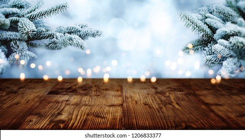 Old rustic wooden table in winter with golden bokeh and rime covered fir branches for a christmas decoration