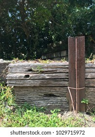 Old rustic wooden timber held up by an iron post, outdoor.