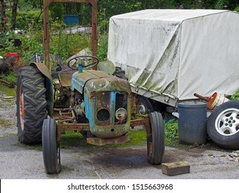 an old rusting abandoned tractor next to a dirty tarpaulin covered trailer and junk in a farmyard