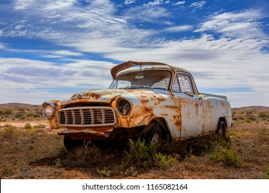 An old rusting relic of a ute left in scrub of Australian outback desert.