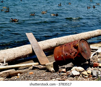 An old rusty 55-gallon drum is knocked over on its side mere inches from the waters of Lake Erie