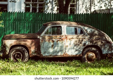 An old rusty abandoned car outdoors broken
