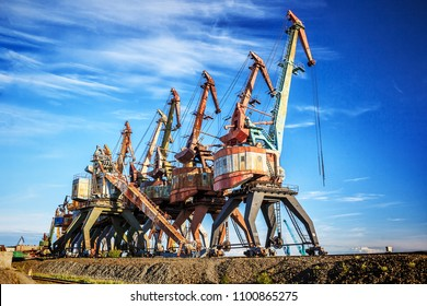 Old rusty abandoned port cranes on the blue sky background, Dudinka, Taimyr, Russia