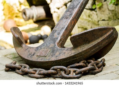 an old rusty anchor with a large rusty chain