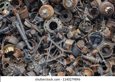 Old and rusty automotive parts are stacked together. Old and rusty iron scrap.
