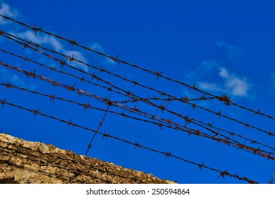 Old rusty barbed wire fence atop concrete wall