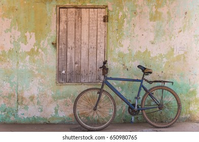 An old rusty bicycle leaning against the wall of a house in the village of Albadarr in the Gambia