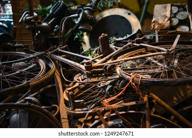 Old rusty bikes, bicycles, retro car details and other vintage items lying in a heap and waiting for their museum restoration. Selective focus