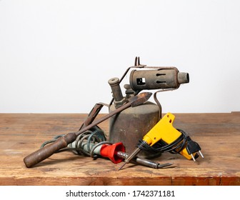 Old rusty blowlamp, soldering iron and electrical soldering devices on a workbench