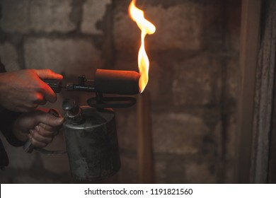 Old rusty blowtorch with fire in male hands