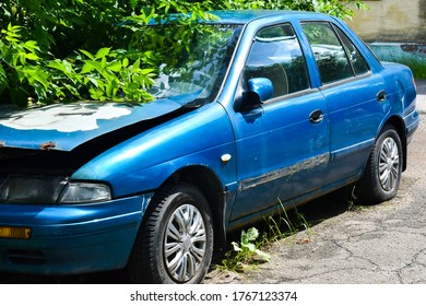 An old rusty blue car is waiting for repairs on the grass. Rusty European avto.
