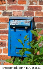 Old Rusty Blue Letter Box on a red Brick Wall