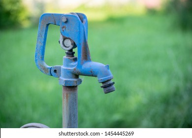 Old, Rusty, Blue Outdoor Water Spigot for a Hose to use in the Yard or on the Lawn