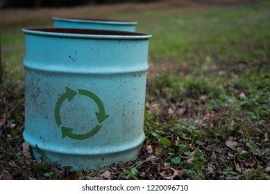 Old rusty blue painted metal compost bin drum barrel compost bin with a green circle recycle logo