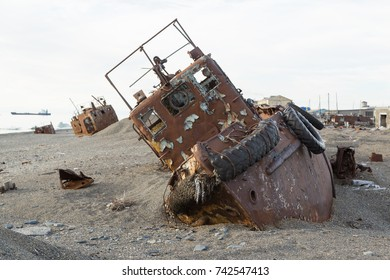 Old rusty boat in sand and a pebble on seacoast