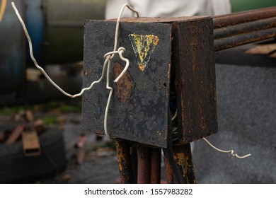 An old, rusty box for connecting wires and cables is full of wires. the lid of the box is tied with a wire. electrical safety violation