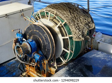 Old and rusty capstan winch of trawler fishing boat with fishing net on it. Equipment for fishing and trawling