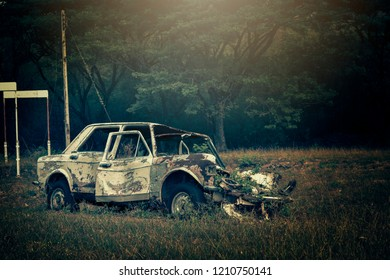 Old rusty car in the centre of the village after war.Abandoned vehicle dumped in countryside field.