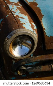 Old, rusty car wreck front and lamp detail