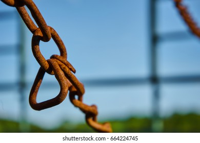 Old rusty chain of a wagon in front of a blue sky background