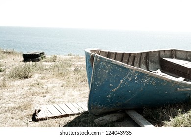 Old rusty classic vintage wood boat on the beach. Sea travel and fishing concept