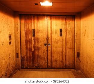 Old and rusty closed elevator doors in a dark hallway