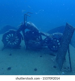 the old rusty creepy scary haunted ghost motorcycle wreck under deep blue sea in scuba divingn trip working as artificial coral reef mor marine life to conservative environment
