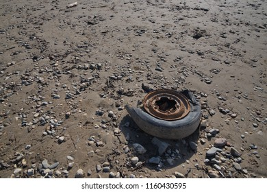 Old rusty distorted vehicle's wheel and tire abandoned on the dark sand of riverbank.