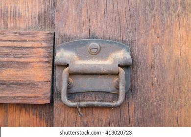 Old and rusty door lock/knob on wooden door - close up