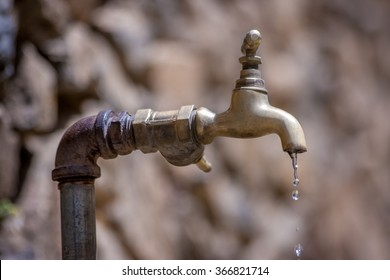 Old, rusty, dripping brass tap