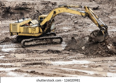 Old rusty earth digging excavator machine working at building construction site