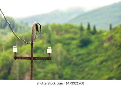 Old Rusty Electric Power Riser Pole, Wires with Electrical Tape, Insulators on Misty Wooded Mountains Background.