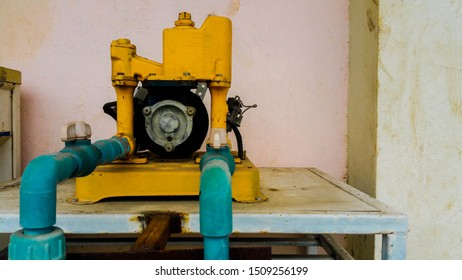 An Old Rusty Electric Water Pump. The Broken Yellow Water Pump, Taken with the smartphone, close-up of old blue valve on the yellow pipe,  A valve for controlling the output of liquids, selective focu