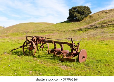Old Rusty Farmers Tiller in Empty Field, Green Grass, Mountain and Sky