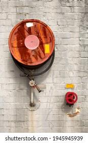 Ancienne bobine de tuyau d'incendie rouillé et soupape d'arrêt rouge montée sur un mur extérieur de bâtiment