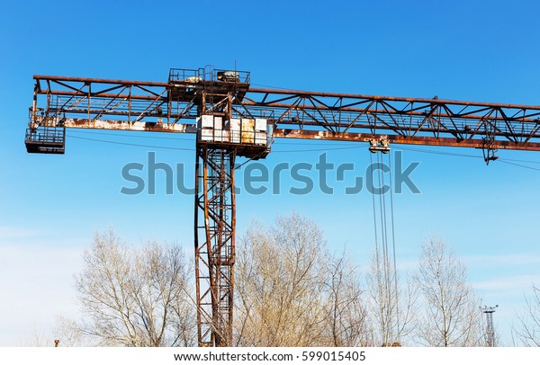 Old, rusty gantry crane on railroad, an abandoned concrete plant. Crisis, collapse of economy, and shutdown of production capacities have led to collapse. Global catastrophe.
