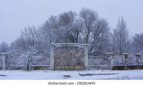 Old rusty gate close way to abandoned park. The ancient fence covers snow. Cloudy winter day. The sleet stuck around everything around