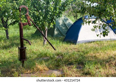 Old rusty hand water pump on a background of the tent camp in the trees