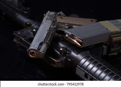 old rusty handgun and assault rifle black background