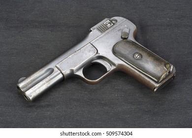 Old rusty handgun on black background