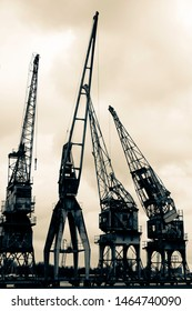 Old and rusty harbour cranes put together in a row and facing different directions. Vintage filter used to create a nostalgic effect.