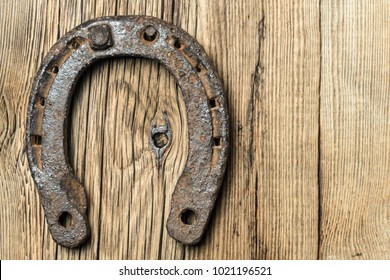 Old rusty horseshoe on a old wooden background
